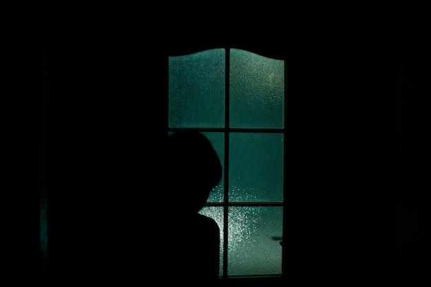 Silhueta escura de uma pessoa através de uma porta de vidro