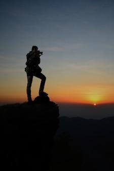 Silhueta escura do fotógrafo do homem no nascer do sol do penhasco e da beleza na manhã.