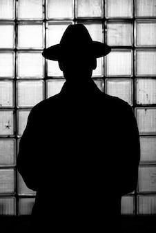 Silhueta escura e mística de um homem com um chapéu à noite no estilo retrô noir