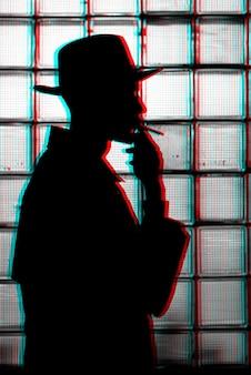 Silhueta escura e mística de um homem com um chapéu fumando um cigarro. preto e branco com efeito de realidade virtual de falha 3d