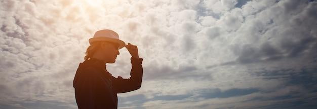 Silhueta feminina em perfil com chapéu na mão contra o céu misterioso com nuvens