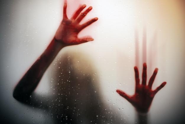 Silhueta garota assustada mão com sangue vermelho por trás da porta de vidro, fundo de horror