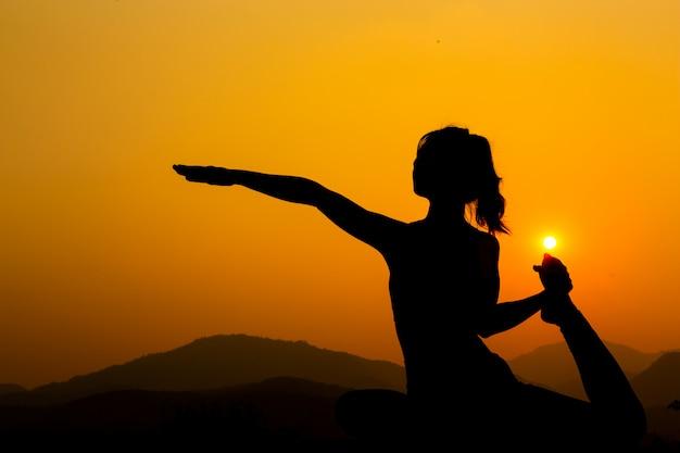 Silhueta - garota do yoga está praticando no telhado ao pôr do sol.