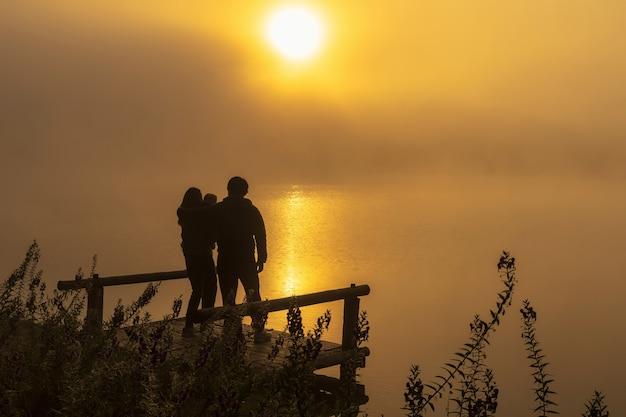 Silhueta homem deprimido sentado no lago do rio de casa flutuante