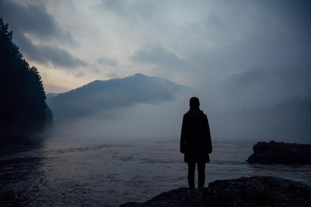 Silhueta humana sozinha na névoa branca contra as montanhas e o rio. nevoeiro espesso no crepúsculo da noite. atmosfera misteriosa. reflexão, meditação.