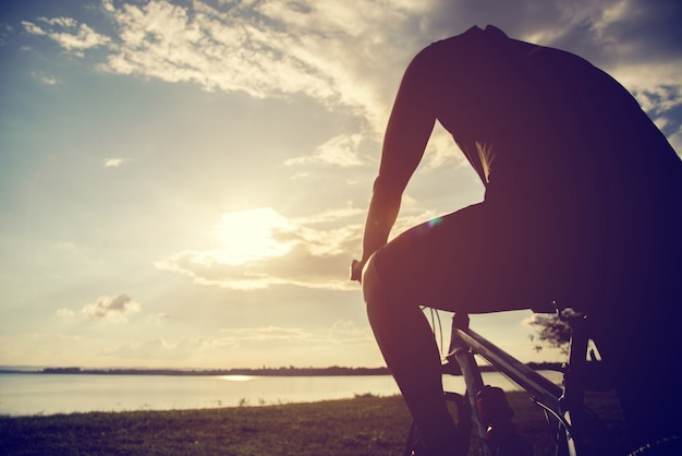 Silhueta jovem de andar de bicicleta no fundo por do sol