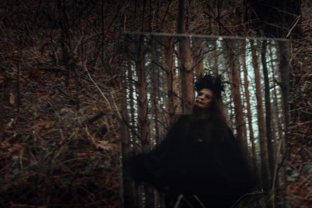 Silhueta mística borrada de uma bruxa terrível e malvada em um espelho em uma floresta escura