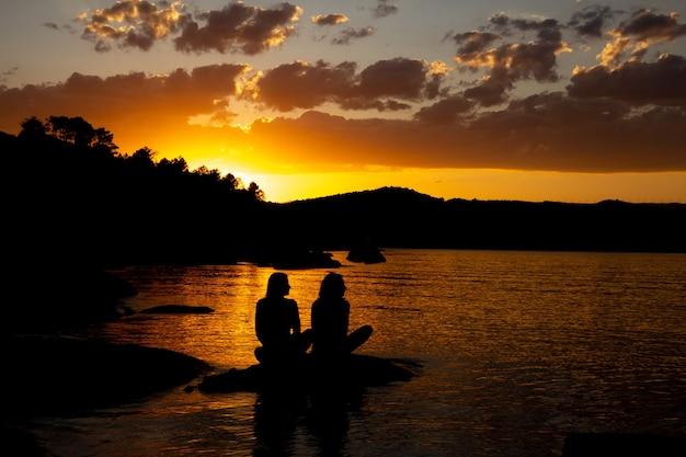 Silhueta negra de dois amigos sentados em um lago por do sol dourado. copie o espaço.