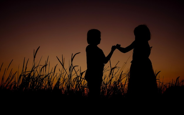 Silhueta negra de dois asiáticos menina em pé sobre um fundo de campo de grama de lindo pôr do sol. a garota dando promessa e mostra a linguagem de sinais de mão.