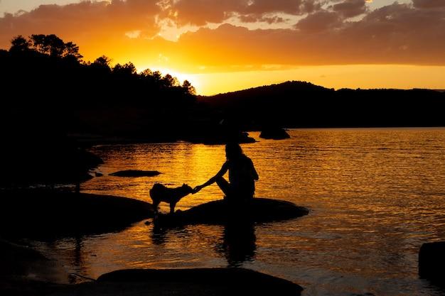 Silhueta negra de jovem brincando com o cachorro. pôr do sol dourado. copie o espaço.