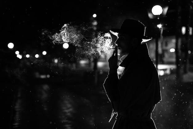 Silhueta negra de um homem de chapéu fumando um cigarro na chuva em uma rua noturna no estilo de noir