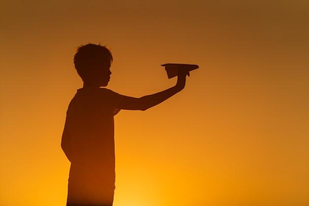 Silhueta negra de um menino em pé contra o fundo laranja do pôr do sol de verão