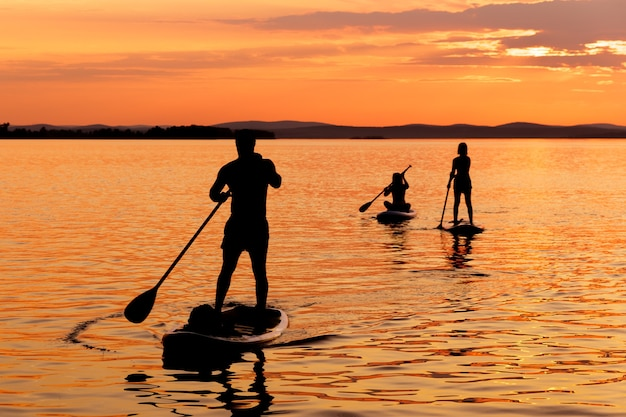 Silhueta negra do pôr do sol com pai, mãe e filha, esportista, remando em stand up paddleboard