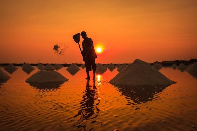 Silhueta o cultivo de sal nas províncias costeiras de phetchaburi, na tailândia, edita o tom quente.