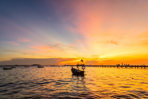 Silhueta pequeno barco de pesca na costa no pôr do sol na praia de bang phra, sriracha choburi, tailândia