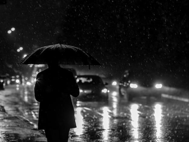 Silhueta preto e branca de um homem com um guarda-chuva nos faróis à noite durante uma chuva torrencial.
