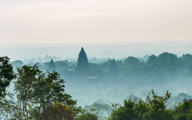 Silhueta principal da fachada do dia ensolarado de angkor wat entre a floresta verde enevoada