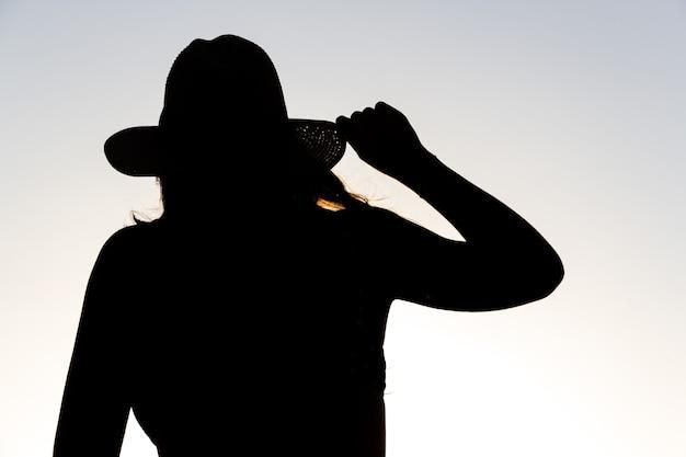 Silhueta retroiluminada de uma mulher segurando um chapéu com uma das mãos.
