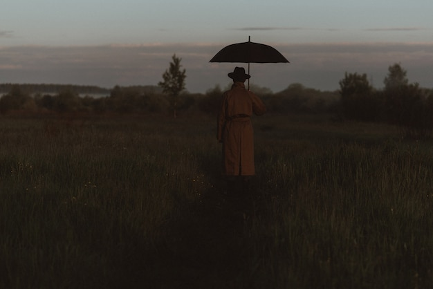 Silhueta surreal de um homem de terno com um guarda-chuva, em uma capa de chuva em um campo. o conceito de liberdade