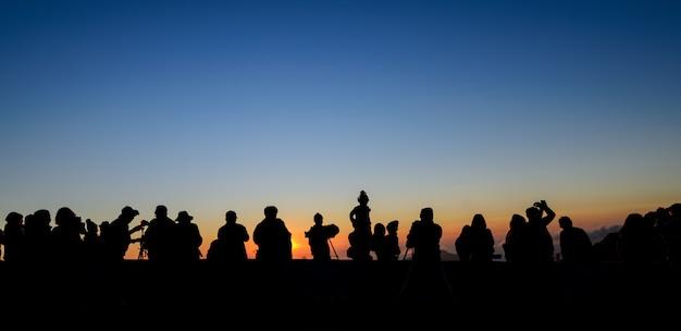 Silhueta turistas e fotógrafos com belo nascer do sol