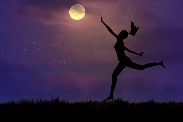 Silhueta, uma jovem mulher segurando a lua na pastagem aberta, o conceito persegue sonhos.