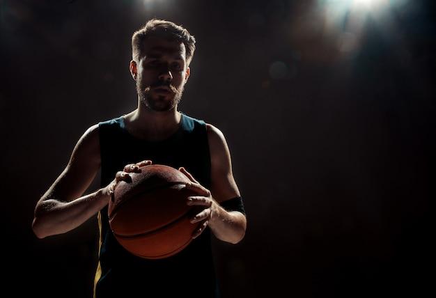 Silhueta, vista de um jogador de basquete, segurando uma bola de basquete na parede preta