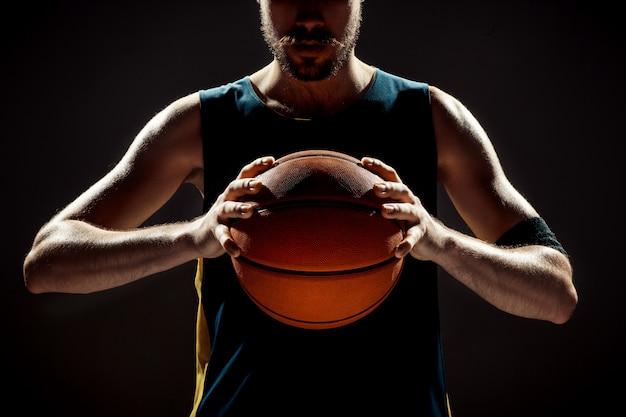 Silhueta, vista de um jogador de basquete, segurando uma bola de basquete no espaço preto