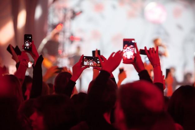 Silhuetas da multidão de concerto na frente de luzes brilhantes