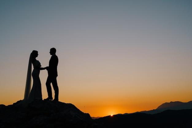 Silhuetas da noiva e do noivo em pé na montanha, contra o fundo do pôr do sol