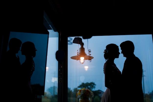 Silhuetas da noiva e do noivo no fundo da janela