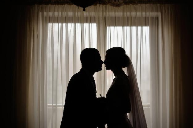 Silhuetas da noiva e do noivo no fundo de uma janela