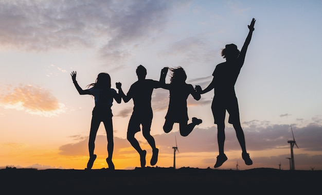 Silhuetas de amigos felizes pulando no pôr do sol