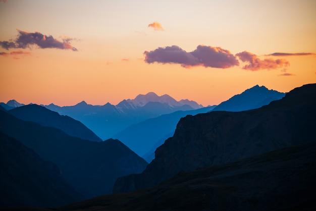 Silhuetas de belas montanhas e céu gradiente dourado com nuvens lilás.