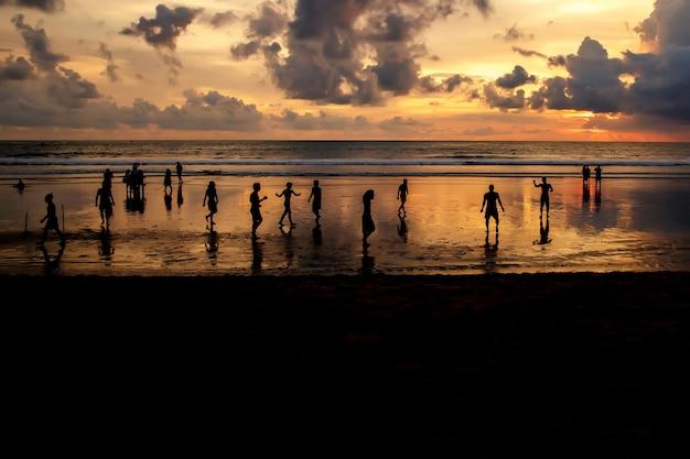 Silhuetas de caras que jogam futebol ao pôr do sol na praia do oceano.
