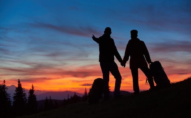 Silhuetas de casal apaixonado, apreciando o pôr do sol enquanto caminhavam montanhas juntos