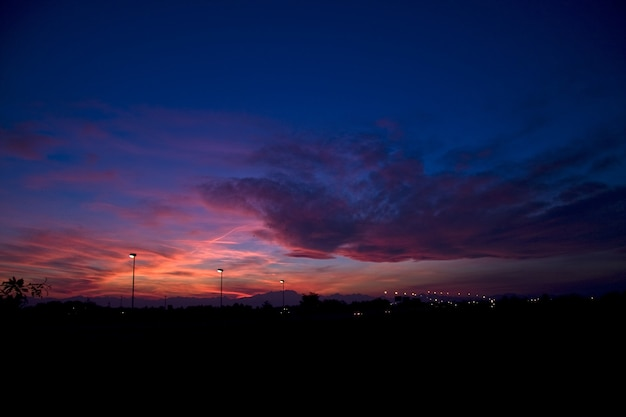 Silhuetas de colinas e postes de luz sob um céu nublado durante um lindo pôr do sol