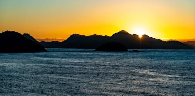 Silhuetas de colinas e rochas à beira-mar durante o pôr do sol no brasil