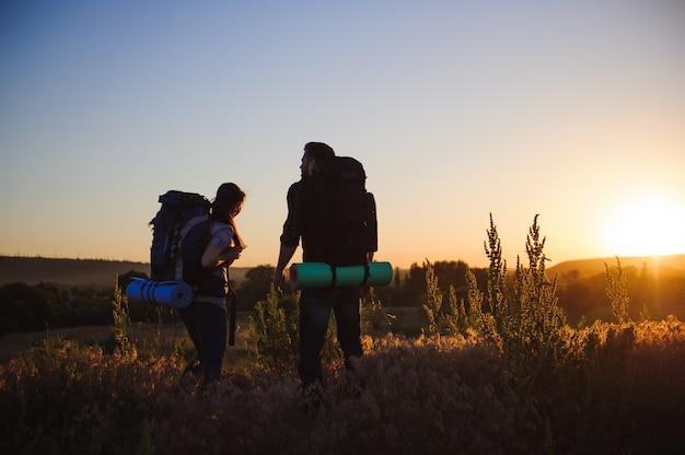 Silhuetas de dois caminhantes com mochilas caminhando ao pôr do sol. trekking e apreciando a vista por do sol.