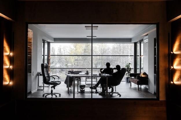 Silhuetas de dois homens, eles estão sentados em um escritório