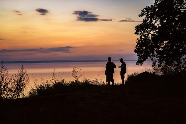 Silhuetas de dois homens na costa antes de um pôr do sol colorido e laranja sobre o mar
