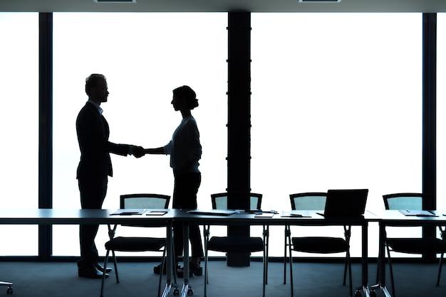Silhuetas de empresário e mulher de negócios apertando as mãos