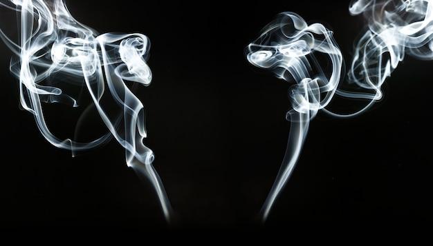 Silhuetas de fumaça branca sobre fundo preto