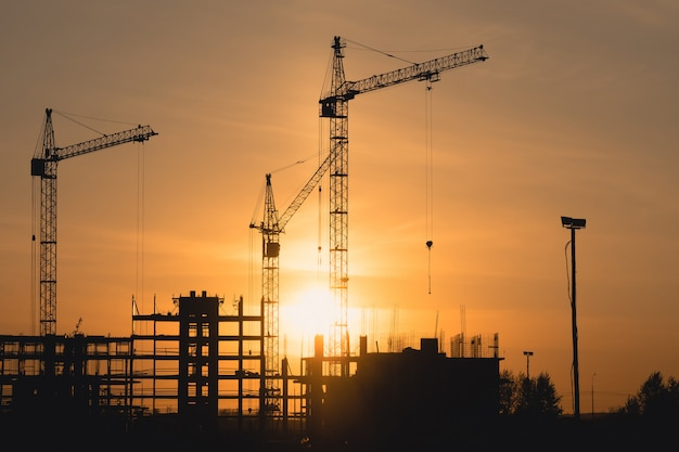 Silhuetas de guindastes de construção ao pôr do sol