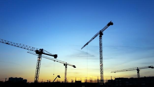 Silhuetas de guindastes de construção no céu azul ao pôr do sol