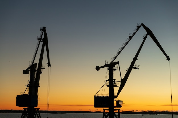 Silhuetas de guindastes no porto à noite ao pôr do sol