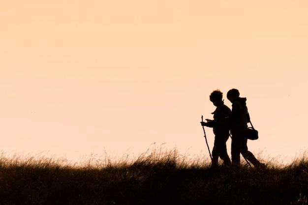 Silhuetas, de, hikers, com, mochilas, desfrutando, pôr do sol, vista, de, topo, de, um, montanha