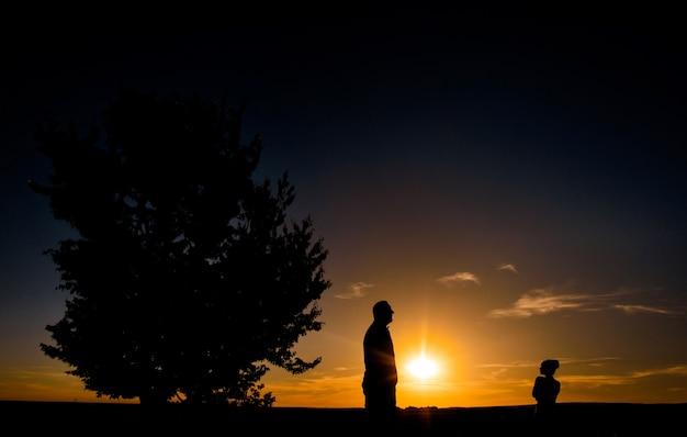 Silhuetas de homem e menina de pé em um campo antes de um por do sol