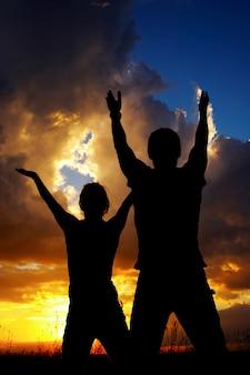 Silhuetas de homem e mulher fazendo ioga ao ar livre ao nascer do sol