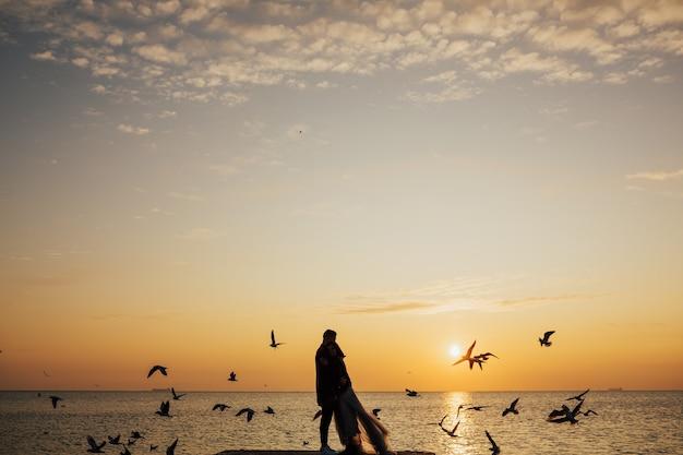 Silhuetas de jovem casal ao pôr do sol cênico na praia tropical.