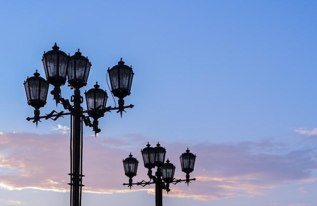 Silhuetas de lâmpadas de rua do ferro forjado contra o céu do por do sol do verão.